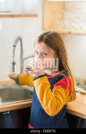 9-year-old girl drinking tap water. - Stock Photo