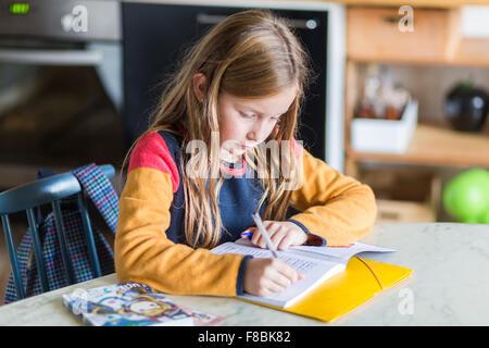 9-year-old girl doing her homework. - Stock Photo
