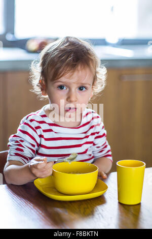24 month old baby girl eating alone. Independence training. - Stock Photo