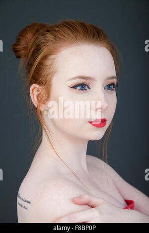 Portrait of a redheaded woman with her hair tied up in a bun. - Stock Photo
