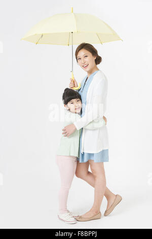 Mother and daughter hugging each other and standing under the umbrella both staring forward and smiling - Stock Photo