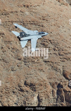 Royal Air Force Tornado GR4 Jet Fighter Flying Close To The Terrain In A Desert Valley. - Stock Photo