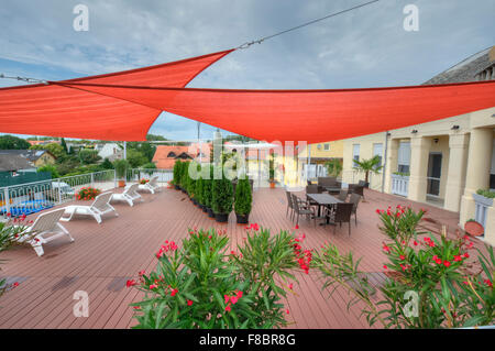 Terrace in summer with shade sails, flowers and deck chairs - Stock Photo