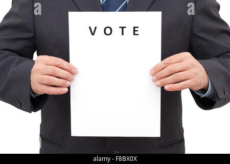 Man in suit, holding a white sheet with title VOTE in front of him. The image has been made in studio and isolated - Stock Photo