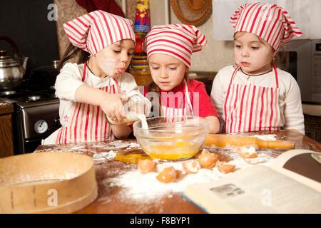 Three little chefs enjoying in the kitchen making big mess. Litt - Stock Photo
