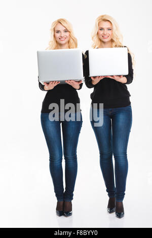 Two positive young blonde sisters twins with laptop computers over white background - Stock Photo