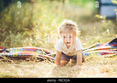 little girl crawling on the lawn - Stock Photo