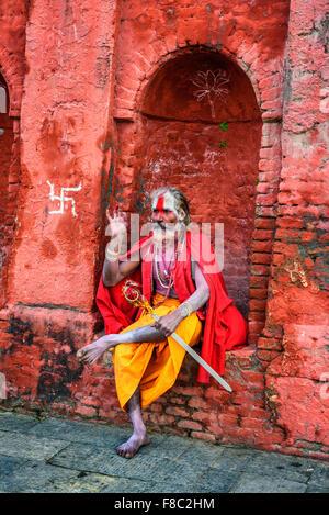 KATHMANDU, NEPAL - OCTOBER 21, 2015 : Wandering  Shaiva sadhu (holy man) with traditional face painting in ancient - Stock Photo