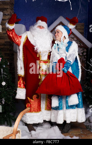 Russian Christmas characters: Ded Moroz (Father Frost) and Snegurochka (Snow Maiden) with gifts bag studio shoot - Stock Photo