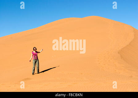Woman standing on a sand dune near Ouarzazate under bright sunlight and a blue sky - Stock Photo