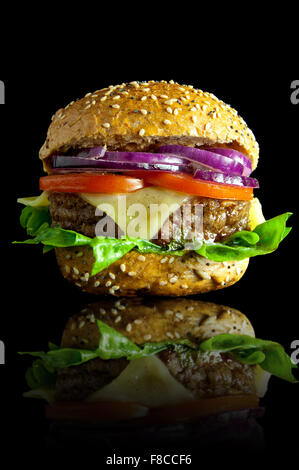 Freshly made burger with melted cheese, onions, tomatoes and lettuce filling - Stock Photo