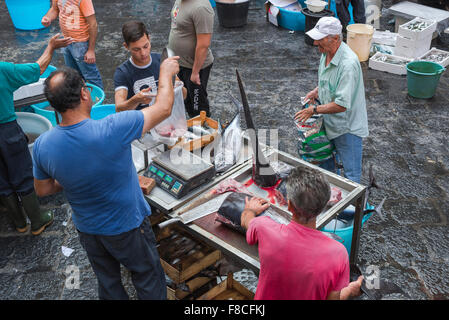 Catania fish market, view of a man buying swordfish on a busy morning in Catania's famous fish market (Mercato della - Stock Photo