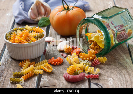 Various types of coloured pasta on a wooden background - Stock Photo