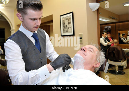 Man receiving shave from barber in Londonderry, Northern Ireland. - Stock Photo
