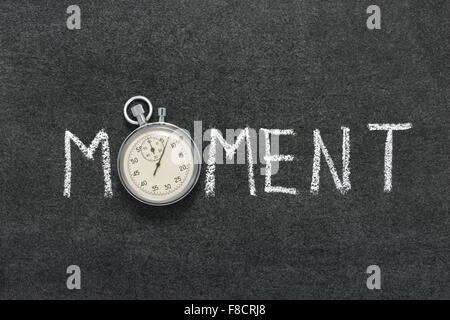 moment word handwritten on chalkboard with vintage precise stopwatch used instead of O - Stock Photo