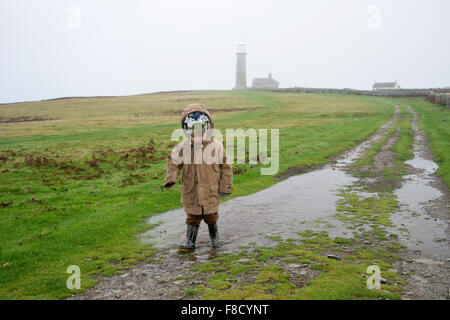 small boy (age 4 - 5) splashing through puddles on Lundy Island, walking from the Old Light lighthouse - Stock Photo