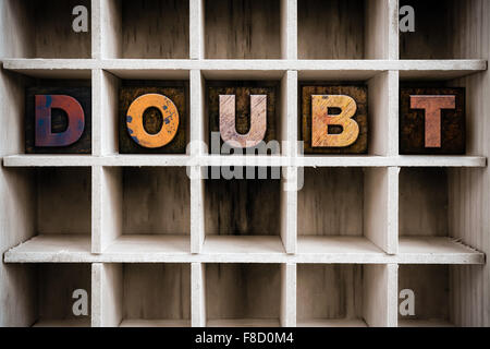 The word 'DOUBT' written in vintage ink stained wooden letterpress type in a partitioned printer's drawer. - Stock Photo