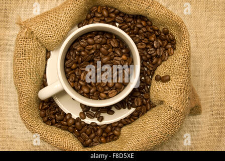 White Cup and Saucer Filled With Coffee Beans Sitting in a Burlap Bag filled with Coffee Beans on a Burlap Background. - Stock Photo