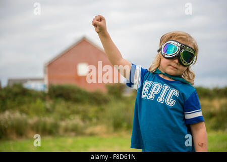 A small pre-teen boy in a home made costume and goggles  dressed up and playing outdoors at being Mini Superhero - Stock Photo