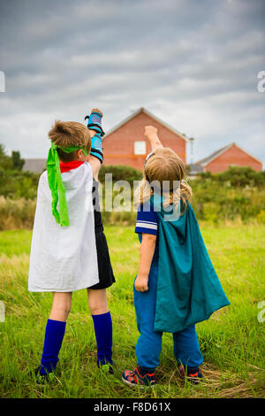 Two boys in home made costumes dressed up and playing outdoors at being Mini Superheroes  on a summer evening , - Stock Photo