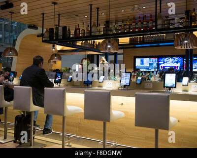 Toronto international airport Terminal 1 departure lounge bar. Tables connected with tablets and iPads for passenger - Stock Photo