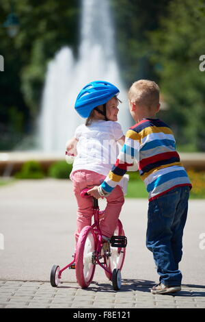 Happy childrens outdoor,  brother and sister in park have fun. Boy and girl in park learning to ride a bike. - Stock Photo
