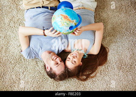 Restful couple with globe making plans for vacation - Stock Photo