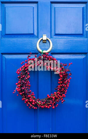 Christmas wreath on a blue coloured wooden door - Stock Photo