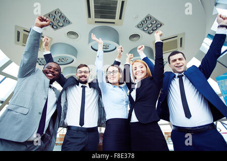 Successful business team standing with raised arms - Stock Photo