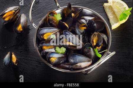 Boiled mussels with lemon on a dark background. Top view