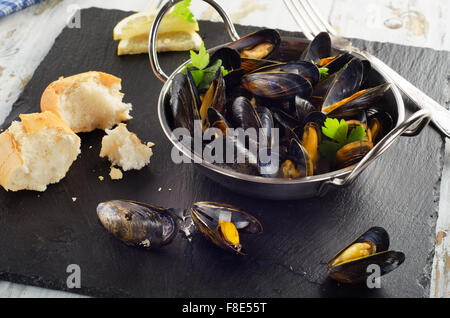 Boiled mussels in cooking dish on dark background. Selective focus - Stock Photo