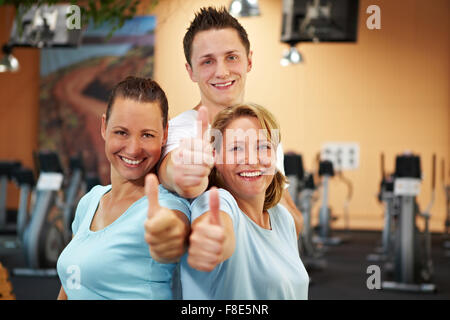Three happy gym employees holding thumbs up - Stock Photo