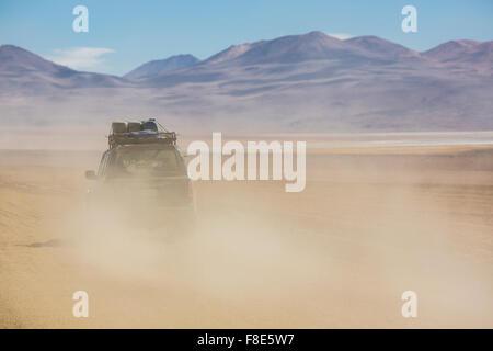 Off-road vehicle driving in the Atacama desert, Bolivia - Stock Photo