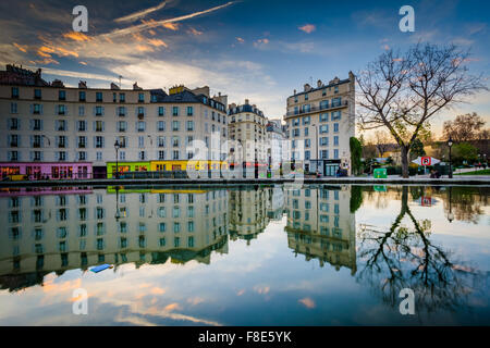 Buildings reflecting in Canal Saint-Martin at sunset, in Paris, France. - Stock Photo