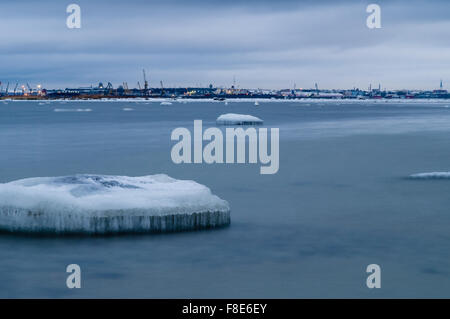 Ice floes of Baltic sea, cargo port on background - Stock Photo