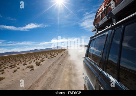 Off-road vehicle driving in the Atacama desert, Bolivia with mountains and blue sky in Eduardo Avaroa Andean Fauna - Stock Photo