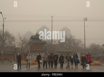 People with face masks wait at a pedestrian crossing on their way to work, braving heavy air pollution in the Chinese - Stock Photo