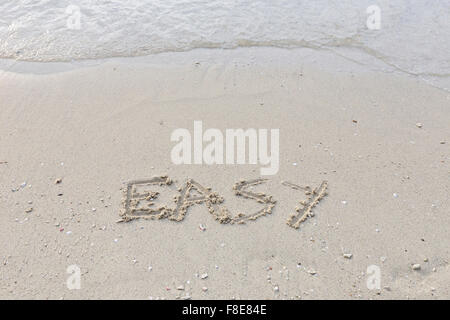 Easy written out in wet sand - Stock Photo