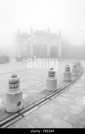 Mountain Gate at the Po Lin Monastery on Lantau Island in Hong Kong, China, at a foggy morning in black&white. - Stock Photo
