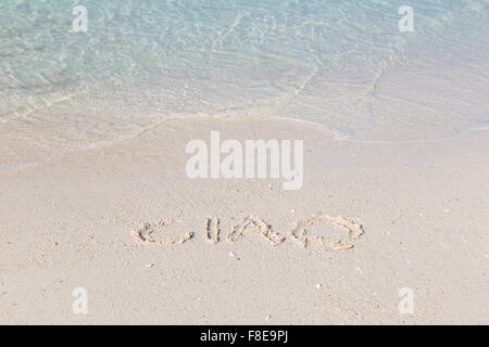 Ciao written out in wet sand on a tropical beach - Stock Photo