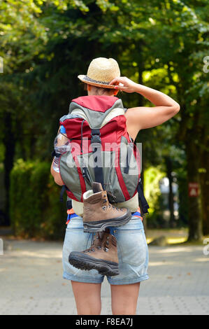 Rear view of female backpacker with straw hat. - Stock Photo