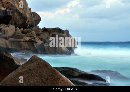 Time lapse view of waves on rocky beach, Seychelles - Stock Photo
