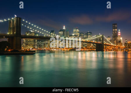 Brooklyn Bridge after sunset at the Blue Hour with view on Manhattan, New York City. - Stock Photo