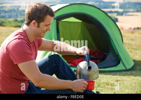 Young Man Camping In The Countryside - Stock Photo
