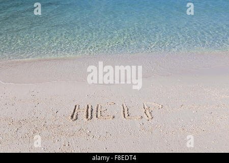 Help written out in wet sand on a tropical beach - Stock Photo