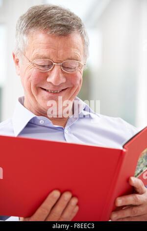 Smiling Senior Man Looking At Photo Album - Stock Photo