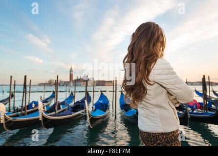Sunset brings to life irresistible magic of Venice - the unique Italian city. Seen from behind, young woman traveler standing on