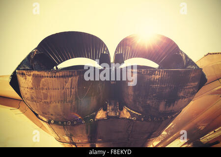 Retro toned jet exhaust pipes against sun. - Stock Photo