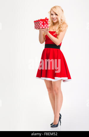 Full length of joyful anticipated young woman in red santa claus costume opening gift over white background - Stock Photo