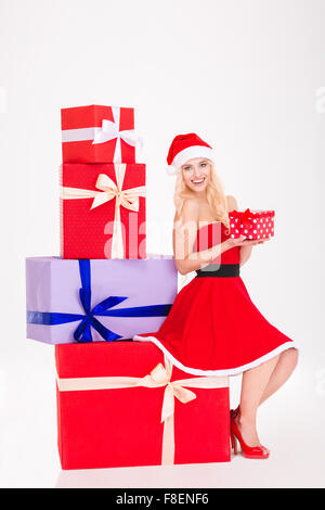 Full length portrait of lovely positive girl in red santa claus dress and hat sitting on present box and holding - Stock Photo